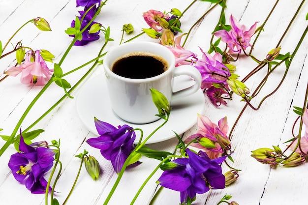 Filiżanka kawy na białym drewnianym stole z różowymi i niebieskimi kwiatami orlików