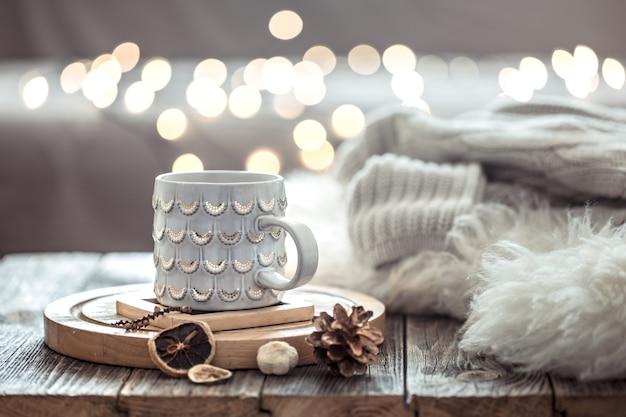 Filiżanka kawy na boże narodzenie światła bokeh w domu na drewnianym stole z swetrem na ścianie i dekoracjami. dekoracja świąteczna