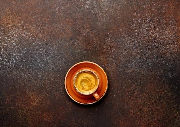 Filiżanka kawy na brązowym tle z pustym miejscem na tekst lub napis.