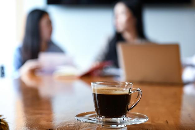 Filiżanka kawy na deak w sali konferencyjnej. niewyraźne tło pracownicy siedzą.