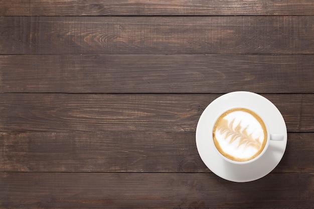 Filiżanka kawy na drewniane tła. widok z góry