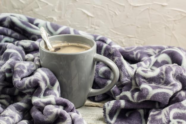 Filiżanka kawy na drewnianym stole i ciepła kratka. koncepcja jesień lub zima