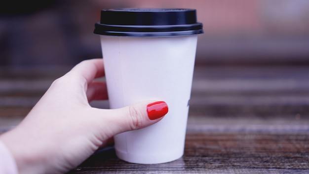 Filiżanka kawy na drewnianym stole w kobiece ręce. kubek papierowy plastikowa nasadka. piękne dłonie z czerwonymi paznokciami