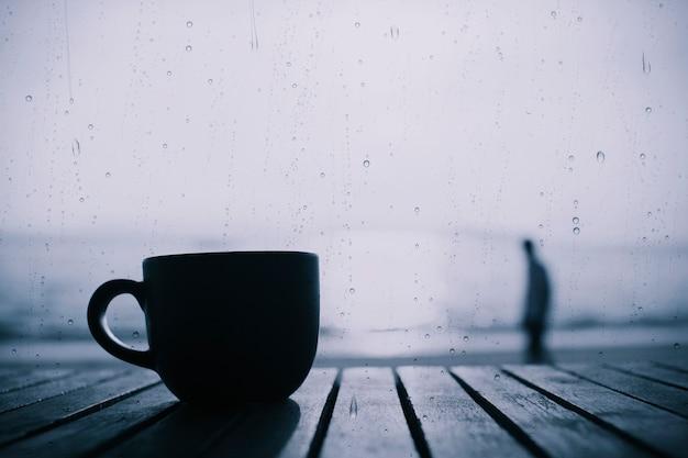 Filiżanka kawy na drewnianym stole w ranku z deszczem opuszcza na szkle