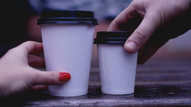 Filiżanka kawy na drewnianym stole w rękach kobiet i mężczyzn. kubek papierowy plastikowa nasadka. czerwone paznokcie