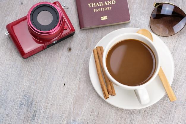 Filiżanka kawy na drewnianym stole w relaksujący dzień do robienia zdjęć, z aparatem, paszportem i okularami przeciwsłonecznymi.
