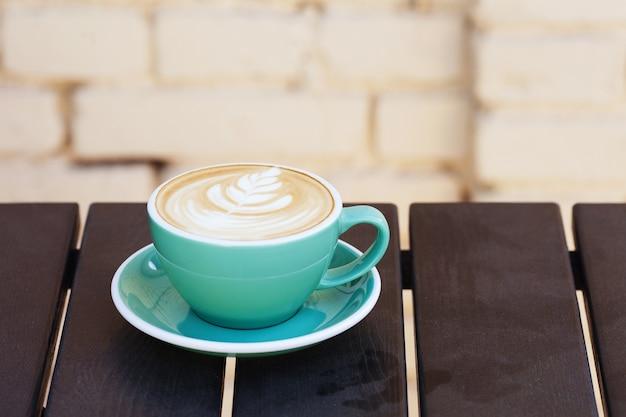 Filiżanka kawy na drewnianym stole. widok z góry.