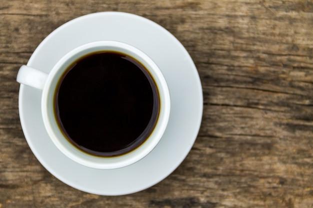 Filiżanka kawy na drewnianym stole. widok z góry