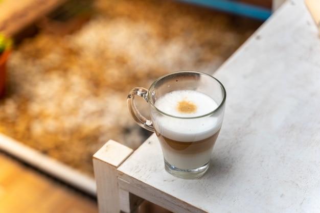 Filiżanka kawy na drewnianym stole z czasem przerwy w pracy, koncepcja żywności. szklanka gorącej coffee latte z ładną mleczną formą z miejscem na kopię