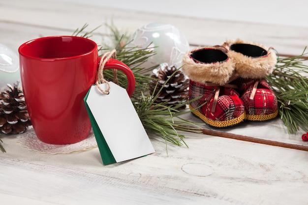 Filiżanka kawy na drewnianym stole z pustą pustą metką i dekoracjami świątecznymi. boże narodzenie koncepcja makiety