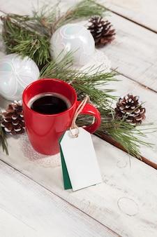 Filiżanka kawy na drewnianym stole z pustą pustą metkę i ozdoby świąteczne.
