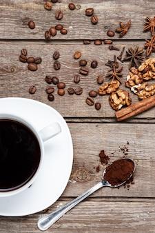 Filiżanka kawy na drewnianym stole z ziarnami kawy, orzechami, laską cynamonu