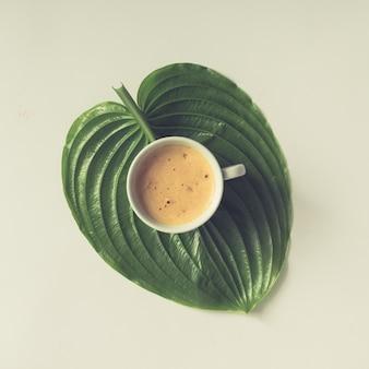 Filiżanka kawy na dużym zielonym liściu. leżał na płasko.