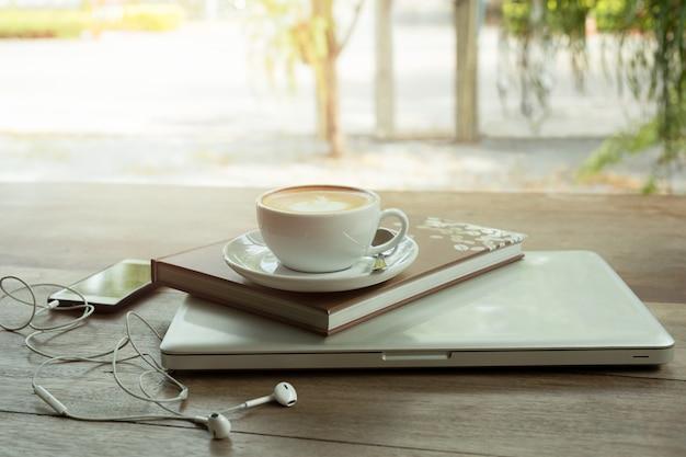 Filiżanka kawy na górze książki i laptopu na drewnianym stole z telefonem komórkowym.