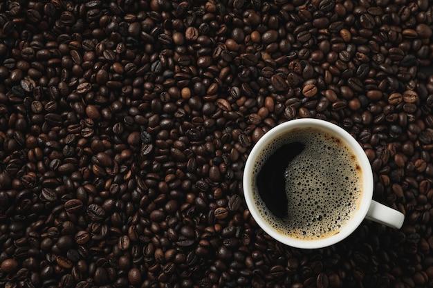 Filiżanka kawy na kawowych fasolach, odgórny widok