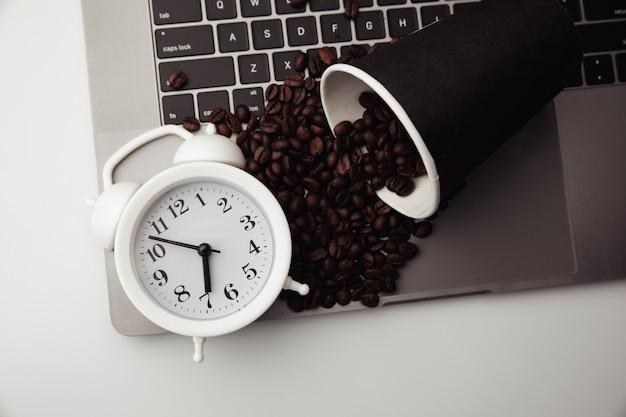 Filiżanka kawy na klawiaturze biały budzik i poranne ziarna kawy w miejscu pracy