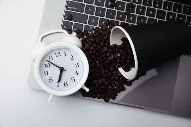 Filiżanka kawy na klawiaturze, biały budzik i ziarna kawy.