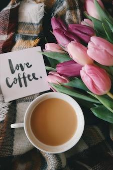 Filiżanka kawy na kratkę w kratę wraz z tulipanami i kartką z życzeniami