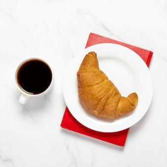 Filiżanka kawy, na książce talerz z rogalikiem na marmurowym stole