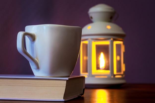 Filiżanka kawy na książce w świetle latarni ze świecą