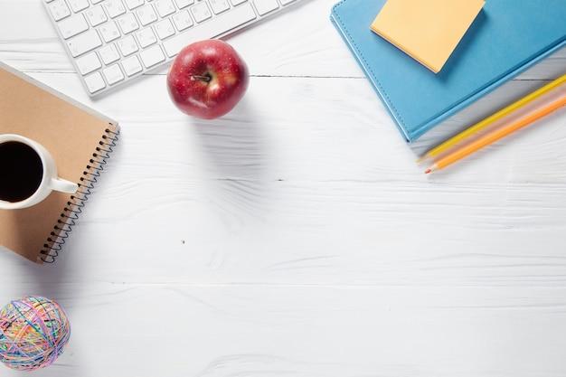 Filiżanka kawy na notesach z klawiaturą komputera i jabłkiem