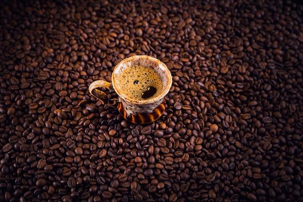 Filiżanka kawy na palonych ziarnach kawy. piękne tło do kawy.