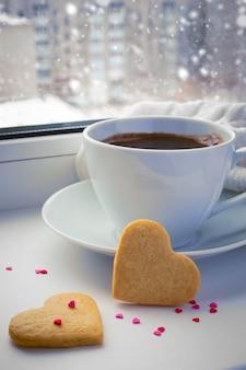 Filiżanka kawy na parapecie zimowym.