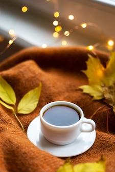 Filiżanka kawy na pomarańczowym swetrze, żółte listki, w tle światełka. ciepła jesień.