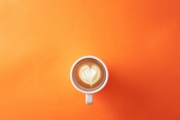 Filiżanka kawy na pomarańczowym tle