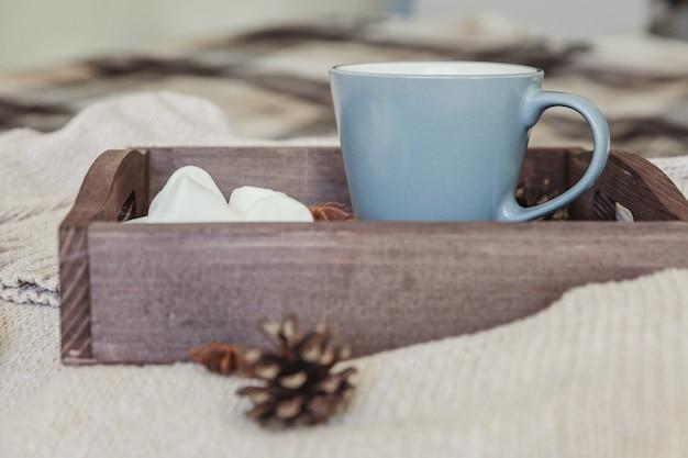 Filiżanka kawy na rustykalnej drewnianej tacy, słodki ptasie mleczko i ciepły wełniany sweter