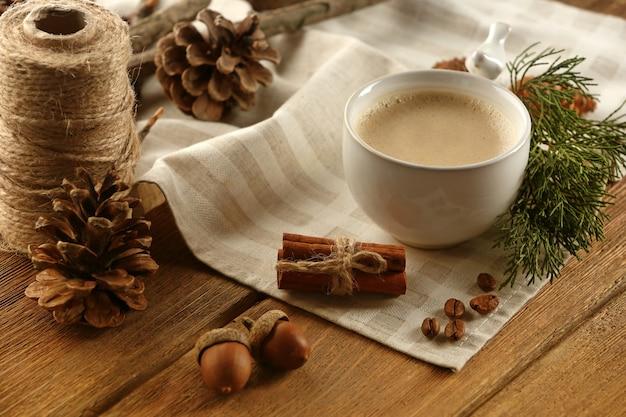 Filiżanka kawy na serwetce na drewnianym tle