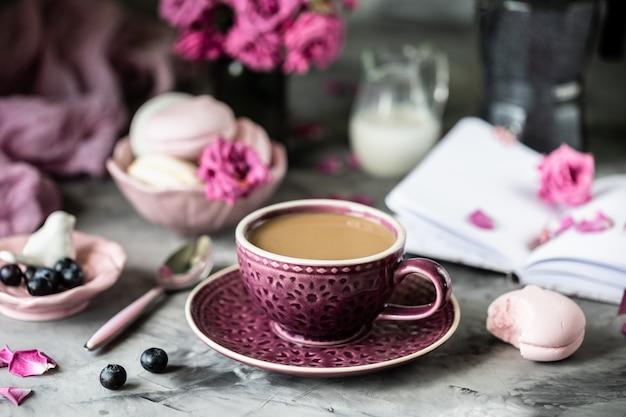 Filiżanka kawy na śniadanie z piankami w postaci ciastek makaronowych w czarnej misce na ciemnym stole i kwiatami w szklance