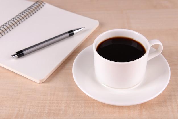 Filiżanka kawy na spodeczku z notatnikiem i długopisem na drewnianym stole