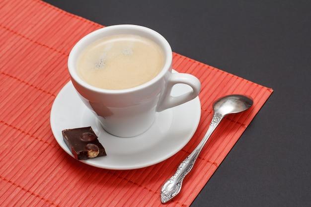 Filiżanka kawy na spodku z kawałkiem tabliczki czekolady, łyżką i bambusową serwetką na czarnym tle. widok z góry.