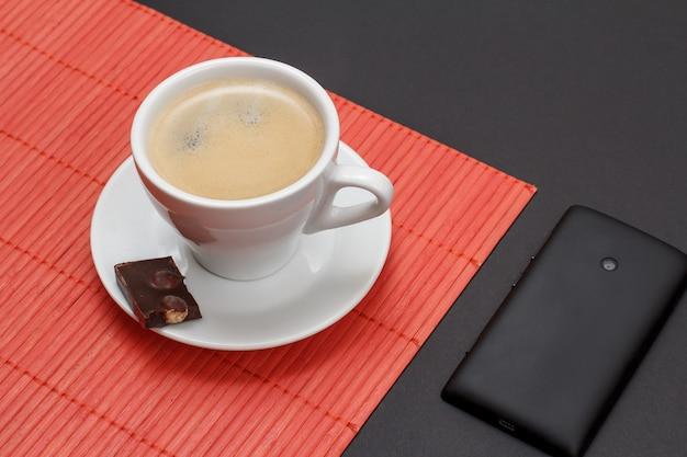 Filiżanka kawy na spodku z kawałkiem tabliczki czekolady na bambusowej serwetce, telefon komórkowy na czarnym tle. widok z góry.