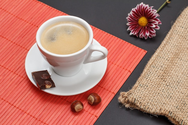 Filiżanka kawy na spodku z kawałkiem tabliczki czekolady, orzechami na bambusowej serwetce, worek parciany i pączek kwiatowy na czarnym tle. widok z góry.