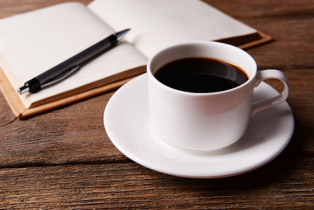 Filiżanka kawy na spodku z notatnikiem i długopisem na drewnianym stole
