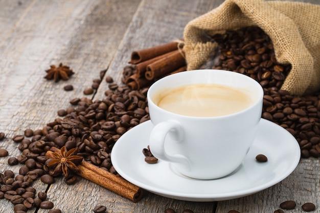 Filiżanka kawy na starym drewnianym stole i worek ziaren kawy
