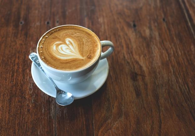 Filiżanka kawy na starym drewnianym stole.