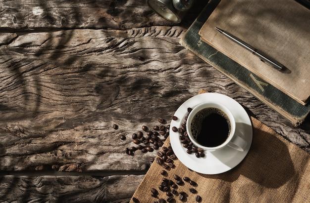 Filiżanka kawy na starym drewnie z cieniem liści palmowych, kawa ze światłem słonecznym