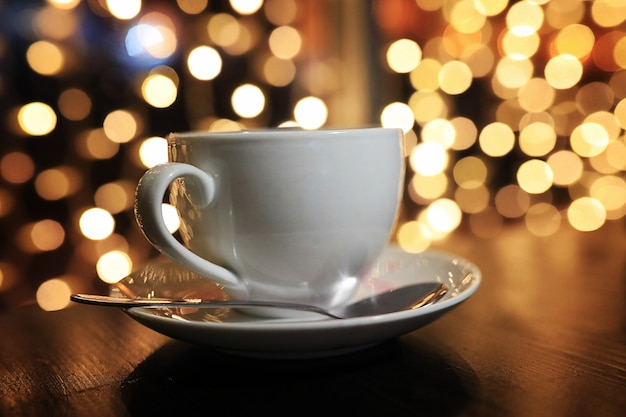 Filiżanka kawy na stole na blured tle z okręgiem bokeh