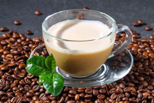 Filiżanka kawy na szarym stole z ziaren kawy i liści kawy