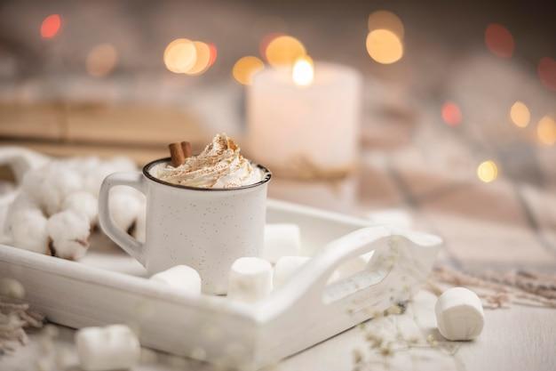 Filiżanka kawy na tacy z piankami i laskami cynamonu