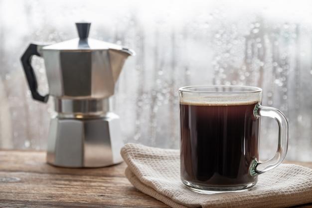 Filiżanka kawy na tle gejzer ekspres do kawy i okno z kroplami deszczu. zbliżenie, selekcyjna ostrość, drewniana powierzchnia