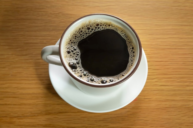 Filiżanka kawy na tle tekstury drewna.
