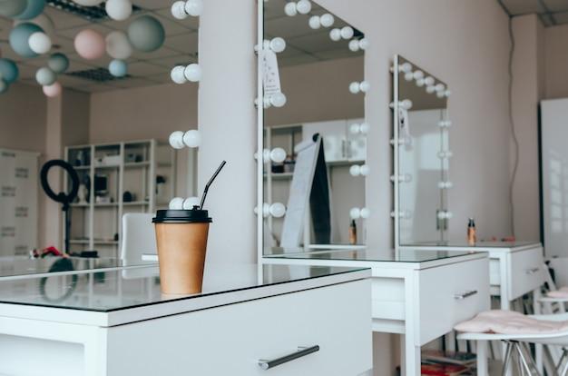Filiżanka kawy na toaletce w pobliżu lustra w pokoju do makijażu