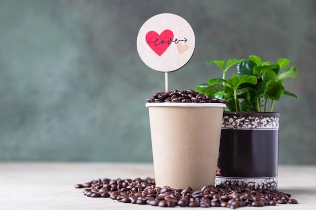 Filiżanka kawy na wynos, drzewko kawowe w garnku i palona kawa ziarnista z miłosnym topperem.