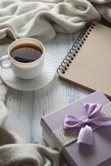 Filiżanka kawy, notatnik, prezent na białym drewnianym stole. pojęcie wiosny