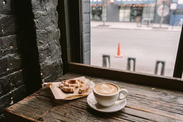 Filiżanka kawy obok ciasteczka postawiona na parapecie