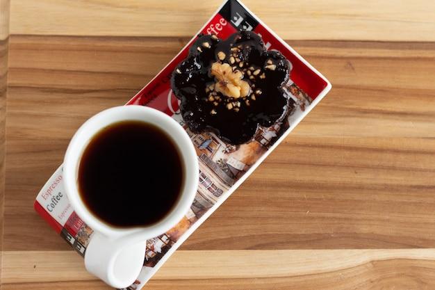 Filiżanka kawy obok czekoladowego cukierka pod drewnianym stołem